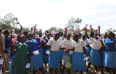 Group of girls holding sanitary pads in the air