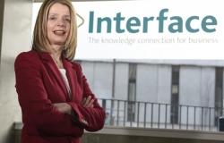 Dr Siobhán Jordan standing infront of Interface logo